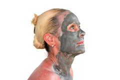 Clay face mask. Portrait of a beautiful elderly woman, making a cosmetic mask of gray clay, isolated on a white background Royalty Free Stock Photography