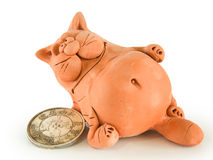 Clay fat cat with coin stock images
