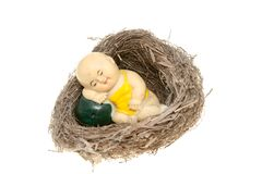Clay figurine in bird nest Stock Image