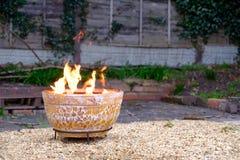 Clay Fire Pit i tillbaka trädgård royaltyfri bild
