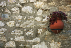 Clay flower pot hanging on an old stone wall in the Spanish vill. Age. Background Royalty Free Stock Photos