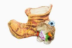 Clay flower pot with a talisman. Brown clay flowerpot in form of shoe with toy-talisman by it Stock Images