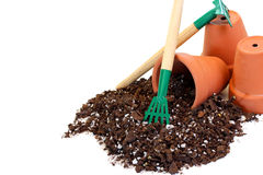 Clay flower pots, soil and a rake for gardening. Stock Photos