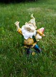 Clay garden gnome with mashroom on a green lawn Royalty Free Stock Images