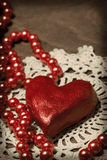 Clay heart and beads on knitted cloth Stock Images