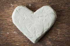 Clay heart on wooden surface Royalty Free Stock Photos