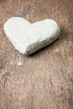 Clay heart on wooden surface Stock Photos
