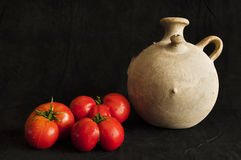 Clay jar and three red tomatoes isolated on black Stock Image