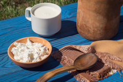 Clay jug, basket, a cup of milkand cottage cheese on a table of Royalty Free Stock Photography