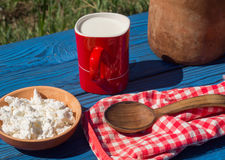 Clay jug, basket, a cup of milkand cottage cheese on a table of Stock Image
