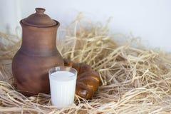 Clay jug with bun and cup Stock Photos