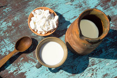 Clay jug, a cup of milk and cottage cheeseon a table of light bl Stock Images