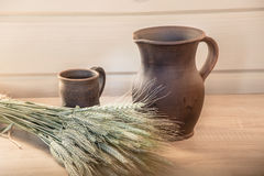 Clay jug and a cup on the table Royalty Free Stock Images