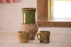 Clay jug and cups. On the table Stock Images