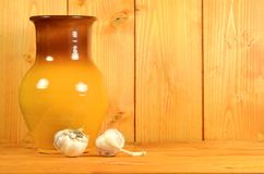 Clay jug and garlic. Still-life with a clay jug and two bulbs of garlic on a yellow wooden background. Free space for text on the right part of the image Stock Photo