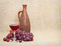 Clay jug with Georgian wine, glass and grapes Stock Images