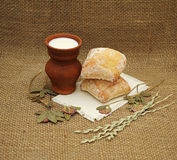 Clay jug with milk, bread and hay. Royalty Free Stock Photo
