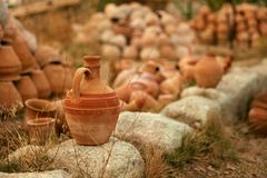 Clay Jug On Stone With Pottery Jars On Background stock photos