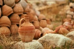 Clay Jug On Stone With Pottery Jars On Background royalty free stock photo