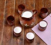 Clay jug and three cups of milk on a wooden table. Stock Image