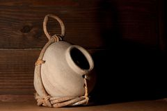 Clay Jug and Twig Birdhouse. Cream colored birdhouse jug partially wrapped in a twig holder held together with leather straps. With a on a dark wooden board as stock photos
