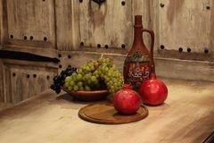 Clay jug for wine and fruit. Jug for wine and fruit on a wooden table Royalty Free Stock Photography