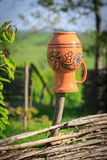 Clay jug on wooden fence Stock Image