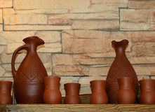 Clay jugs and cups on a shelf Royalty Free Stock Image