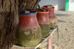 Clay jugs filled with water to drink or wash for hikers and visitors in a village in Sudan royalty free stock photo