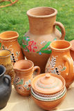 Clay jugs, grass. Pottery with a national ornament on the background of a green glade Royalty Free Stock Photo