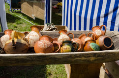 Clay jugs lying in wooden trough at village market Royalty Free Stock Photos