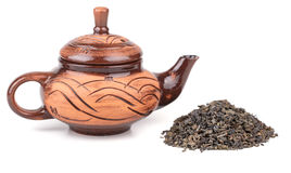 Clay kettle and dry tea leaves Stock Image
