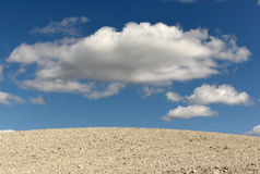 Clay land and white clouds on the blue sky Royalty Free Stock Photo