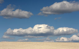 Clay land and white clouds on the blue sky Stock Photo