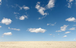 Clay land and white clouds on the blue sky Stock Photos