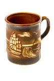 Clay mug handmade with ship. Brown clay cup handmade with the image of the ship and the sea gulls isolated on white background Stock Image