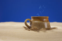 Clay mug with tea or coffee on beach sand Royalty Free Stock Images