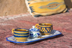 Clay ornamental cups of tea on a carpet Stock Image