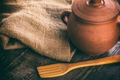 Clay pan on a wooden table. Wooden spoon and sacking. Rustic still life Royalty Free Stock Photo