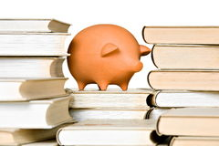 Clay piggy bank and old-fashioned books Royalty Free Stock Photos