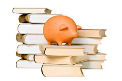 Clay piggy bank and old-fashioned books Royalty Free Stock Photography