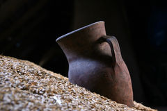 Clay pitcher. On a heap of grain the old jug lies Royalty Free Stock Image