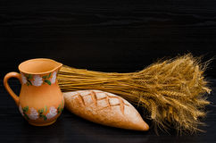 Clay pitcher, rye bread and a sheaf on a black background Stock Photo
