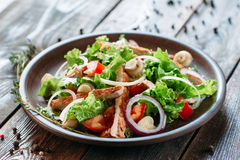 Clay plate with chicken salad on wooden table Royalty Free Stock Photography