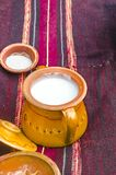 Clay plate pot with sower milk on old traditional ethno red rug Royalty Free Stock Photography