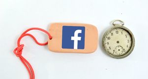 Clay plate and vintage clock with logo of facebook. Image of a clay plate and vintage clock with logo of facebook Royalty Free Stock Image