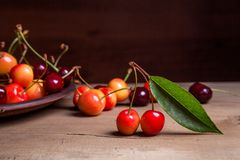 Clay plate with yellow and red sweet cherry on wooden background. Clay plate with berries of yellow and red sweet cherries and several fruit with green leaf of stock photography