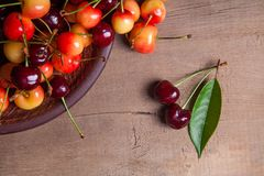 Clay plate with yellow and red sweet cherry on wooden background. Clay plate with berries of yellow and red sweet cherries and several fruit with green leaf of royalty free stock images