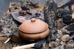 Clay pot on coals royalty free stock images