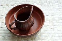 Clay pot on clay basin. An old clay pot in a clay basin, rests on a grass mat Stock Images